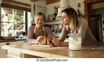 An elderly grandmother with an adult granddaughter making dough at home.