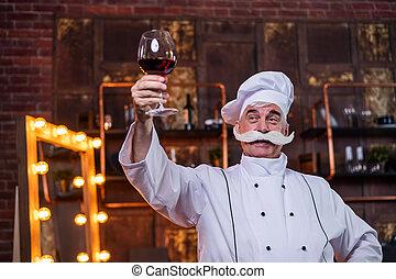 An elderly male chef degustation red wine in the kitchen.