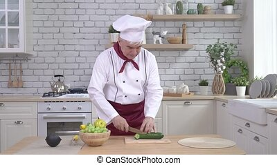 An elderly male chef is cutting a cucumber in the kitchen.