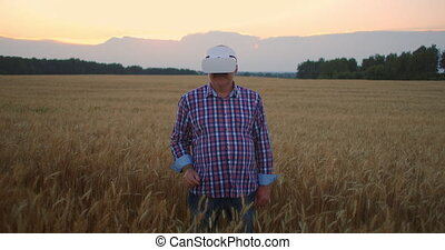 An elderly male farmer uses gestures with his hands standing...