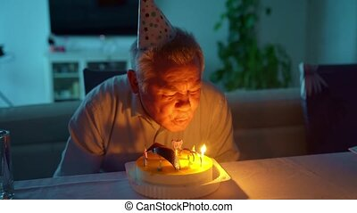 an elderly man blows out candles on the birthday cake. tradition to make a wish. selective focus.