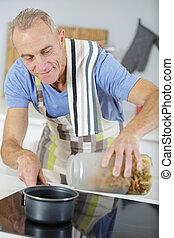 an elderly man cooking pasta