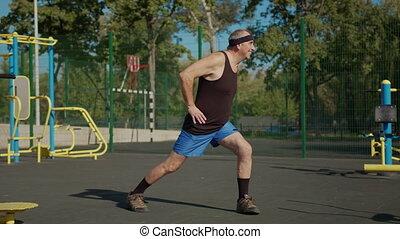 An elderly man doing a warm-up outdoors