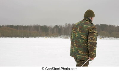 An elderly man enters a frozen lake in the winter and takes...