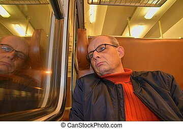 An elderly man in glasses commuting at work. Middle age man looking out of the window of train. Passenger during travel by high speed express train in Europe. An elderly man travelling in train at night