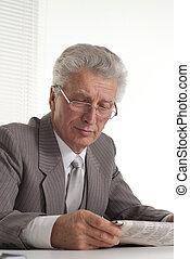 An elderly man in glasses sitting