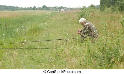 An elderly man is fishing on a small river in the summer. Uses a fishing rod and worms. Forest and high green grass