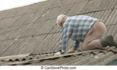 An elderly man is fixing the roof himself. Old wooden house...