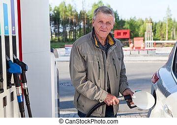 An elderly man is on gas station with fuelling nozzle in hands