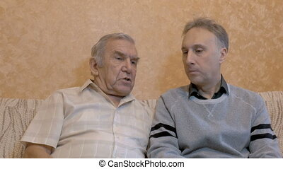 An elderly man is talking with his son. They are sitting on the couch
