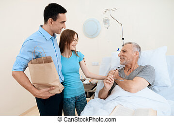 An elderly man lies in a hospital room on a bed. He is seen by a man with a woman. They are standing next to his bunk.