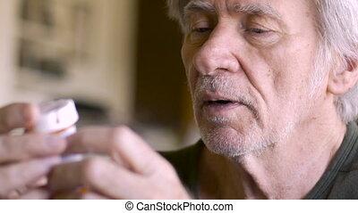 An elderly man reads aloud the instructions on his prescription medicine bottles