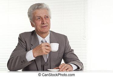 An elderly man sits on a light
