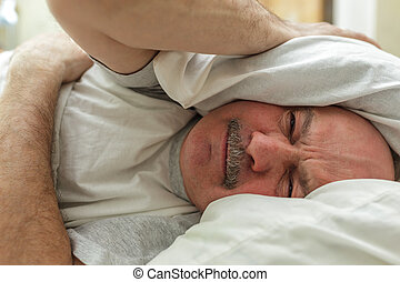 An elderly man suffers from insomnia, trying to sleep