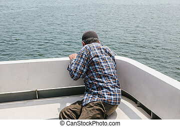 An elderly man swims on a ferry or passenger boat and has an attack of nausea.