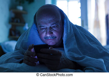 An elderly man tries to fall asleep and checks the mail or calls on the phone. Addiction on the Internet, a problem with sleep