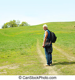 An elderly man with a backpack walking along the road. Elderly man enjoys traveling and photography nature.