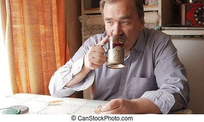 An elderly man with a mustache holds a cup of hot drink and drinks. He sits near the window and has breakfast at home