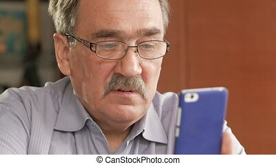 An elderly man with a mustache in glasses dials a text message on his mobile phone. Sits at home at the table.