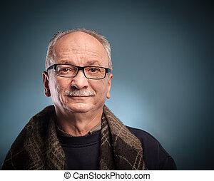 elderly man - An elderly man with glasses looks skeptically