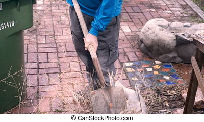 An elderly retired man struggles with a shovel to get a plant out of a pot