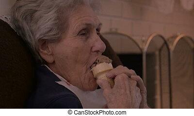 An elderly senior enjoys a chocolate ice cream cone - 90...