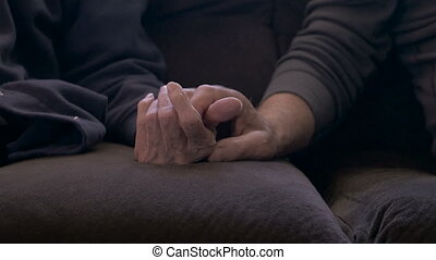 An elderly son holds his mother's hand on a sofa - dolly shot in 4k