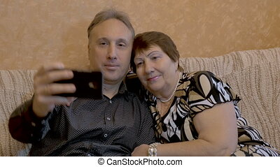 An elderly woman and her adult son are photographed on a smartphone.