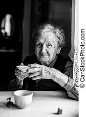 An elderly woman at the table drinking tea from the saucer. Black and white portrait.