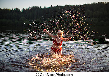 An elderly woman bathes and splashing in the river at sunset.