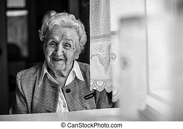 An elderly woman black and white portrait near the window.