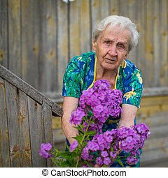An elderly woman caring for flowers