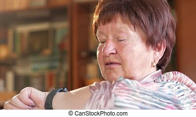 An elderly woman checks the messages on a smart watch. She reads reminders and speaks the phrase for a search. After reading the result