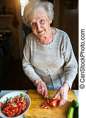 An elderly woman chops vegetables for a salad.