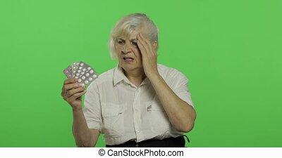 An elderly woman dissatisfied looking at blister pills....
