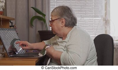An elderly woman embroiders with embroidery scheme on laptop. Online hobby time at home concept