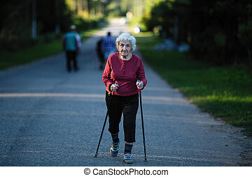 An elderly woman engaged in Nordic walking with sticks.
