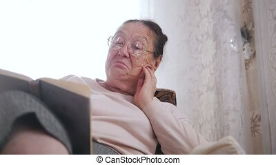 An elderly woman enjoys sitting in a chair and reading aloud...