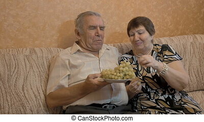 An elderly woman feeds her husband's grapes. They are a happy couple.
