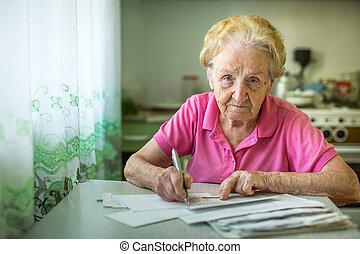 An elderly woman fills in utility bills.