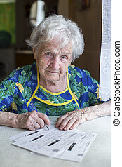 An elderly woman fills out forms
