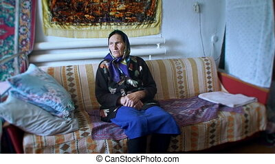an elderly woman in a bright headscarf sitting in the room...