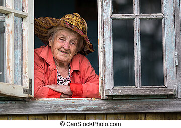 An elderly woman in a straw hat looking from the window of the farmhouse.