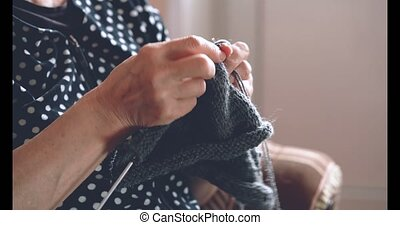 An elderly woman is knitting some socks