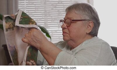 An elderly woman in glasses looking at his embroidery needlework. Hobby time at home concept