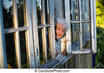 An elderly woman looks from the window of a country house.