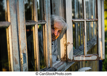 An elderly woman looks from the window of the farmhouse.