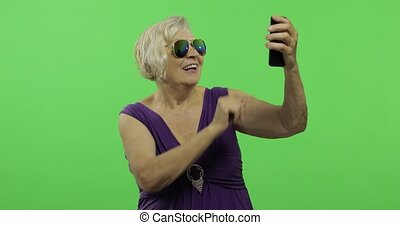 An elderly woman make a photo on a smartphone. Selfie. Chroma key