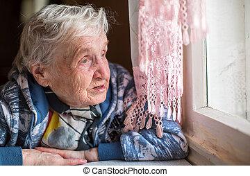 An elderly woman near the window.