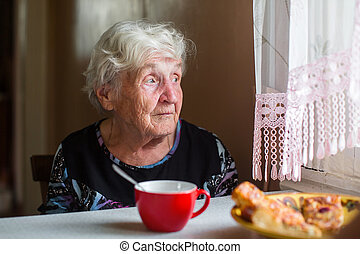 An elderly woman near the window with a Cup of tea.